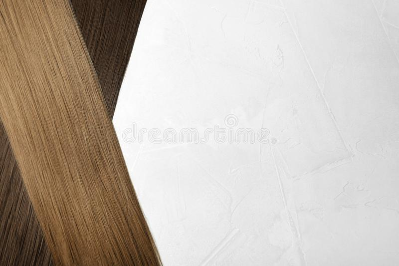 Beautiful straight brown hair on light background, flat lay royalty free stock images