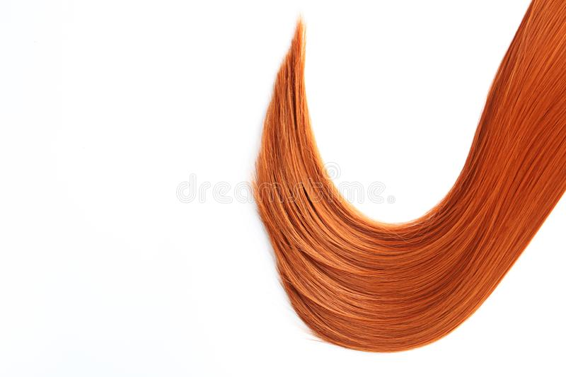Beautiful strand of straight red hair on white background. Hairdresser service. Beautiful strand of straight red hair on white background, top view. Hairdresser royalty free stock image