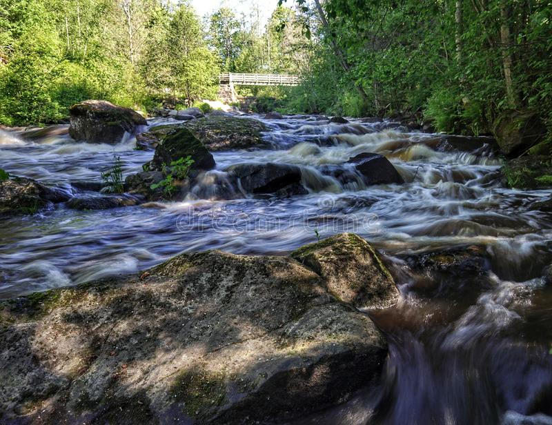 Beautiful  streaming river and big rocks scene. Beautiful  streaming river and  growing in riverbank scene. beautiful  streaming river and waterfall and rocks in royalty free stock images
