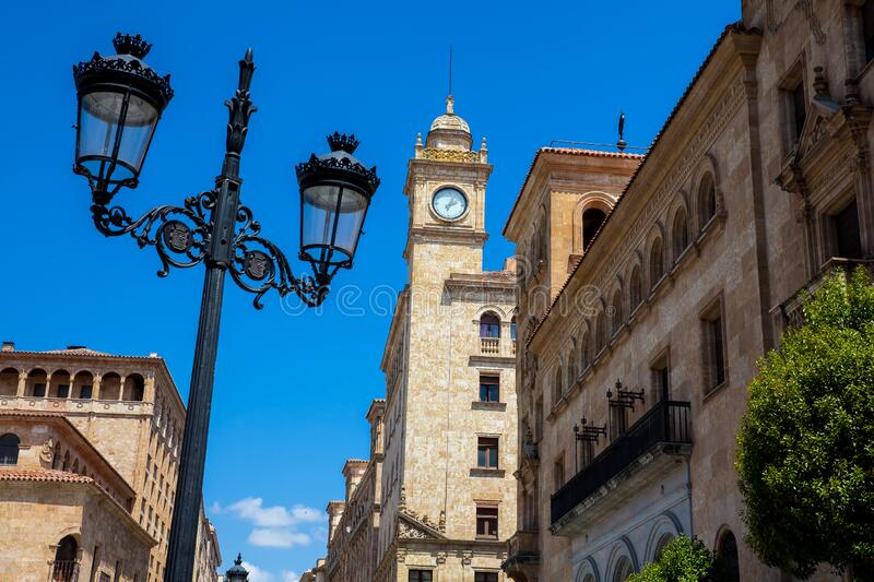 Street lamp and the clock tower of an antique building at Zamora Street in Salamanca city center. Beautiful street lamp and the clock tower of an antique royalty free stock photo