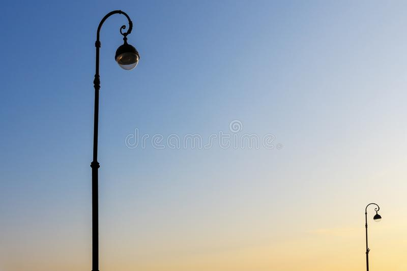 Beautiful street lamps against the blue sky in the early morning in the light of the rising sun. Beautiful street lamps against the blue sky in the early royalty free stock photos