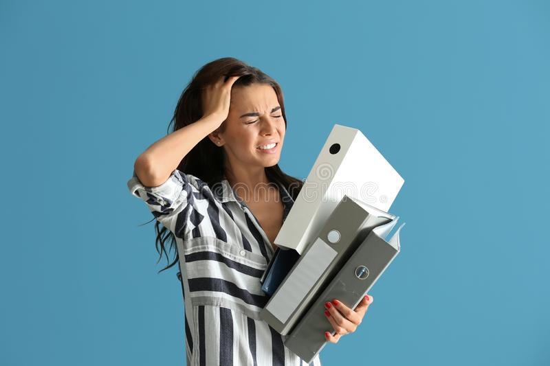 Beautiful stressed businesswoman with folders on color background stock image