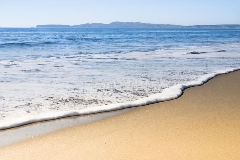 Beautiful stretch of sand and surf. Gentle surf lapping against smooth golden sand with distant hills beyond blue sea stock photography