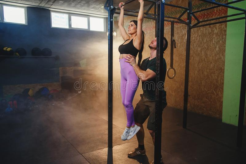 Beautiful strong muscular woman doing pull up exercise with help of personal trainer it the gym. royalty free stock photos