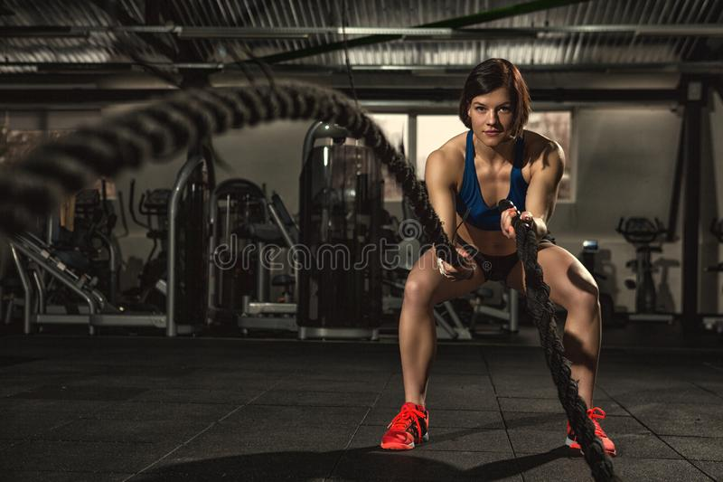 Beautiful strong sporty woman doing crossfit exercise with battle ropes. Battle ropes session. Attractive young fit and toned sportswoman working out in stock photos