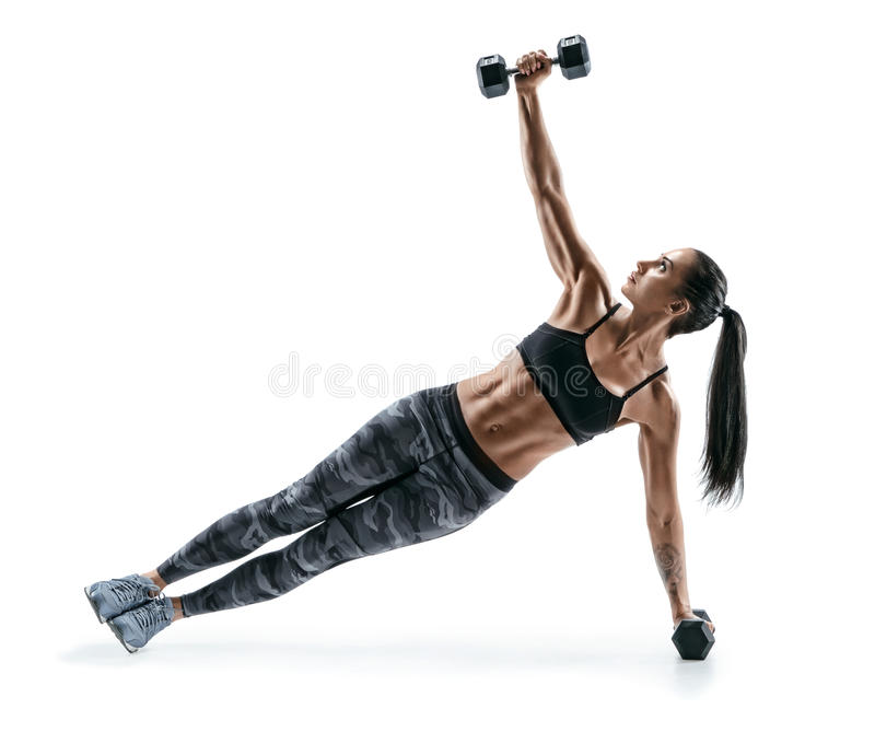 Beautiful strong woman doing fitness plank position exercises with dumbbells royalty free stock photo