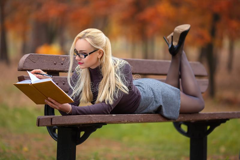 Student girl reading book in the autumn park. Beautiful student girl with perfect legs laying on the bench and reading the book in the autumn park in the lights royalty free stock photos