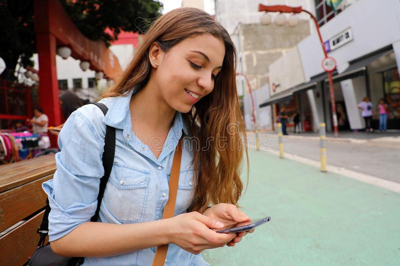 Beautiful student girl sitting on street bench messaging with mobile phone in Sao Paulo City, Brazil.  stock image