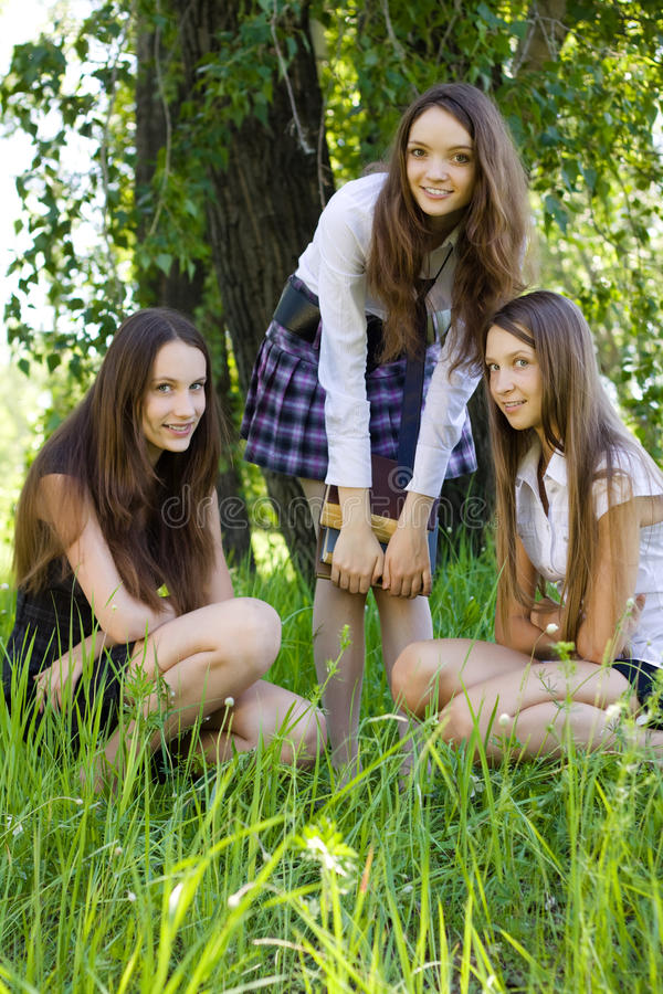 Beautiful student girls with books in the park stock photo