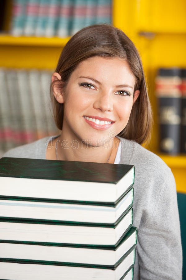 Beautiful Student With Piled Books Smiling In royalty free stock images