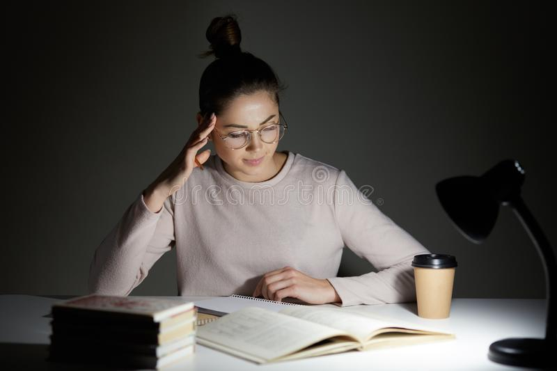 Beautiful student sits at white desk against dark background, tries to concentrate under light of lamp, wears casual jamper and royalty free stock image