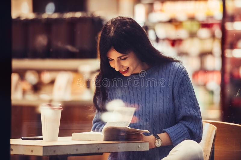 Beautiful student woman reading a book in the cafe with warm cozy interior and drinking coffee stock photography