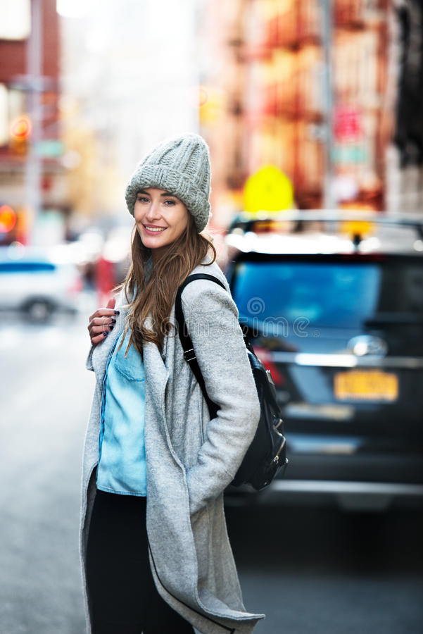 Beautiful student woman ready get in into her car parked on city street. Cute smiling woman wearing autumn casual street style. Outfit and backpack walking on stock images