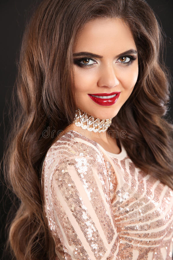 Beautiful stunning brunette smiling woman portrait. Wavy hair st. Yle. Red lips Makeup. Healthy shiny hairstyle. happy girl model in sequin dress on black stock photos