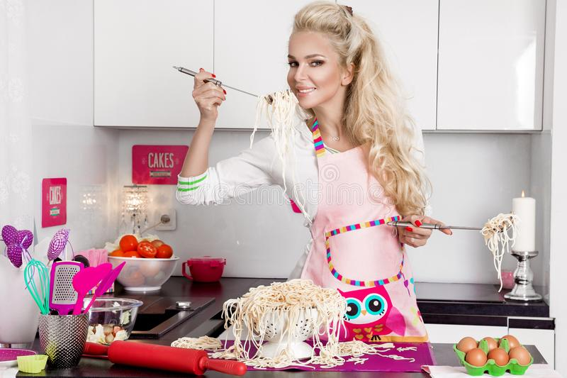 Surprised funny girl with pasta on the head. Beautiful stunning funny blonde woman dressed in costume cook cooks in the kitchen noodles pasta stock photo
