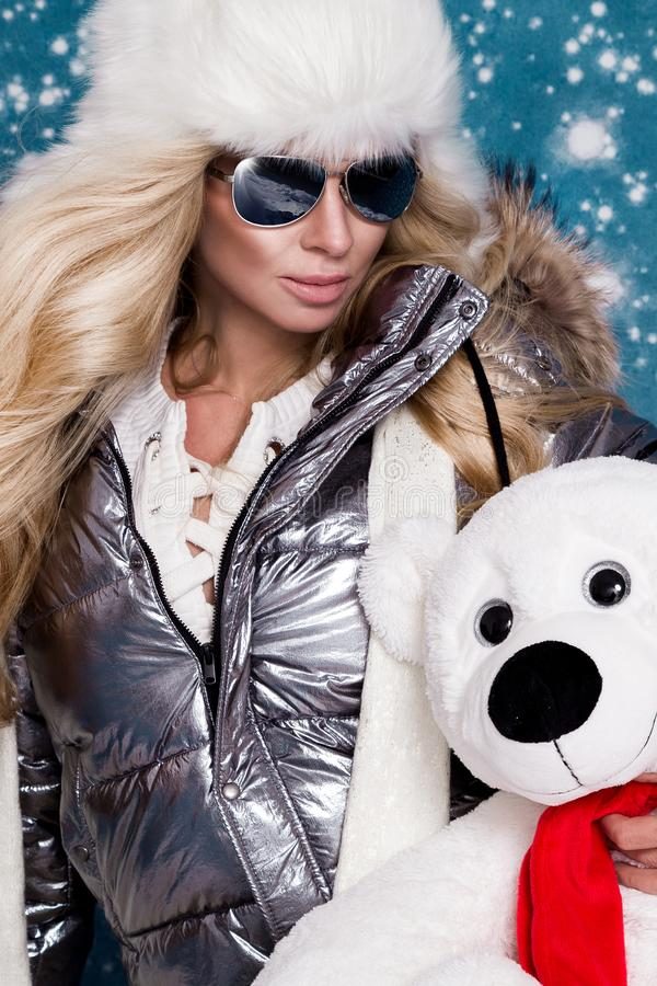 Beautiful stunning woman with long blond hair and perfect face dressed in winter clothing, silver warm jacket and fur cap. And silver sunglasses on winter royalty free stock image