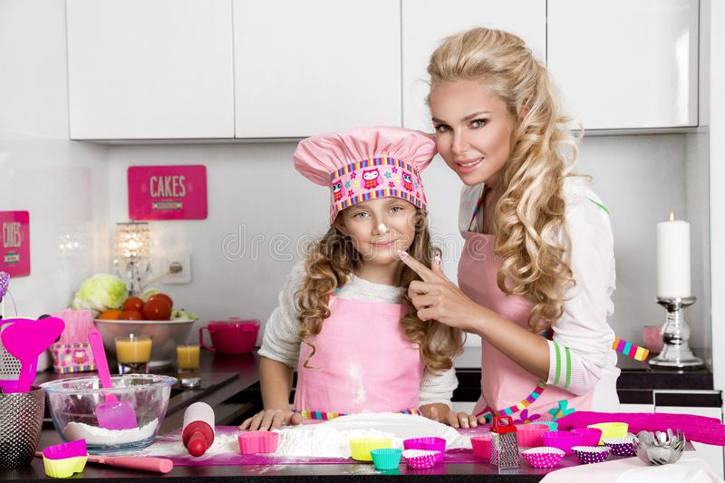 Beautiful stunning woman mother and daughter in aprons kitchen cooking in the kitchen cookies. Beautiful stunning women mother and daughter in aprons kitchen stock image