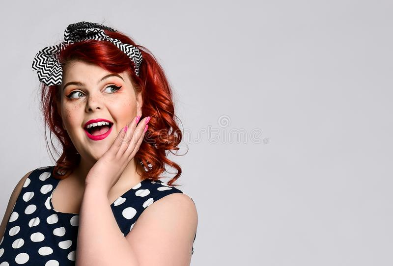 Pin up a female portrait. Beautiful retro fat woman in polka dot dress with red lips and manicure nails and old-style haircut royalty free stock photography