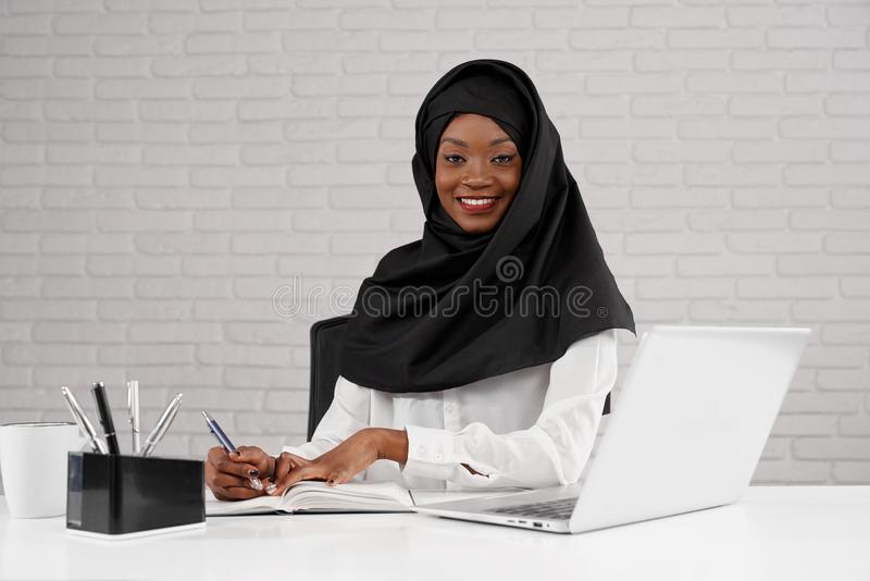 African muslim woman in black hijab posing at workplace. royalty free stock photography