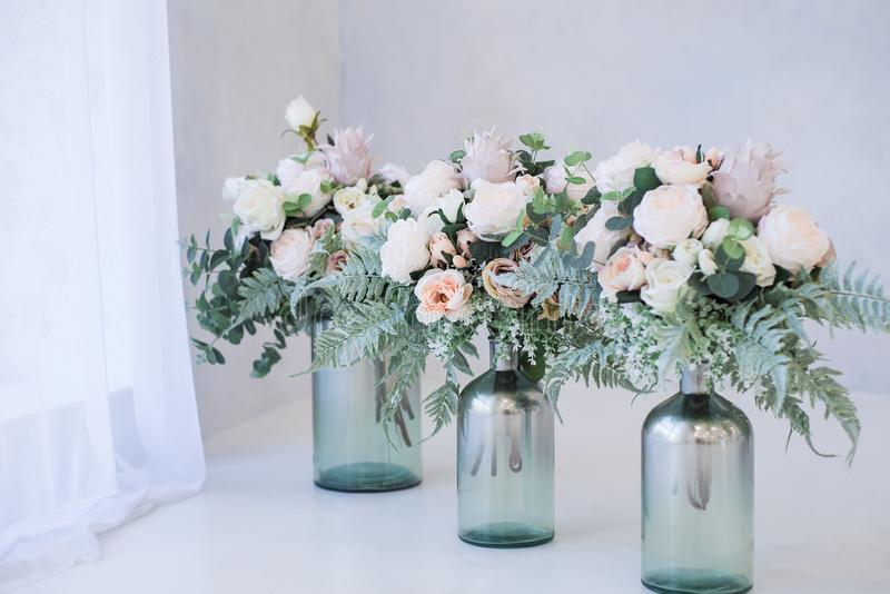 Beautiful and stylish artificial flowers in a glass vases stand on a floor. Flower decor on a white background royalty free stock photography