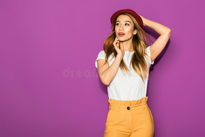 beautiful stylish asian girl in hat posing and looking away stock photography