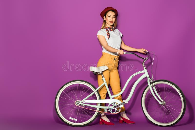 beautiful stylish asian girl standing with bike and smiling at camera stock images