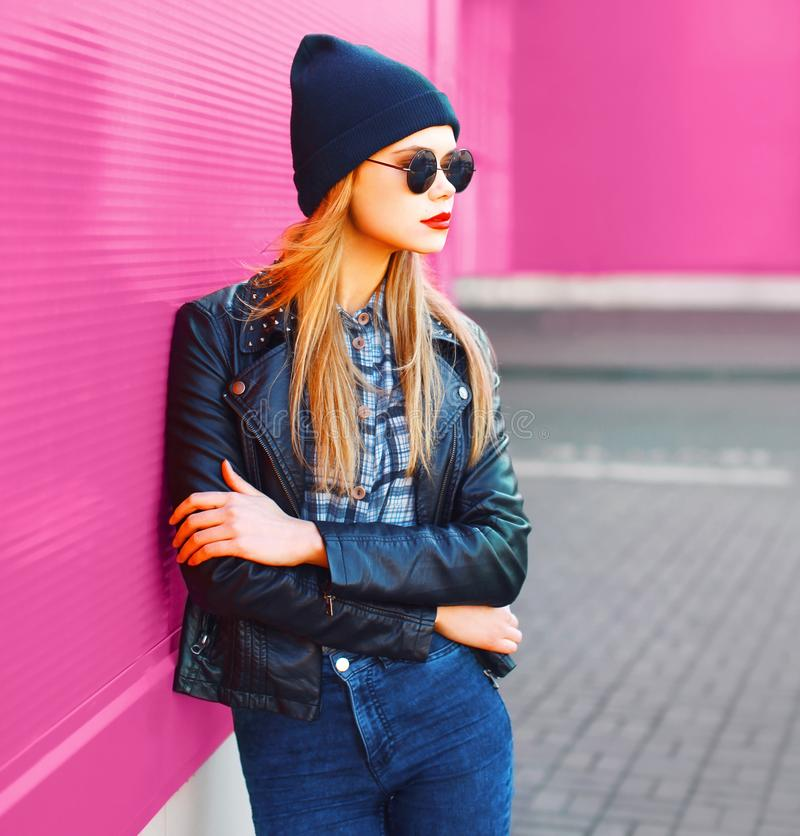 Beautiful stylish blonde woman in profile, wearing rock black style jacket, hat posing on city street over colorful pink wall. Background stock image