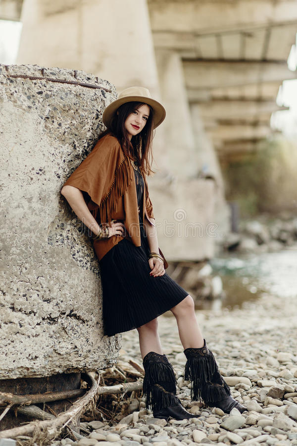 Beautiful stylish boho woman with hat, fringe poncho and boots. Girl in gypsy hippie look young traveler posing near river rocks in mountains. sensual look stock images