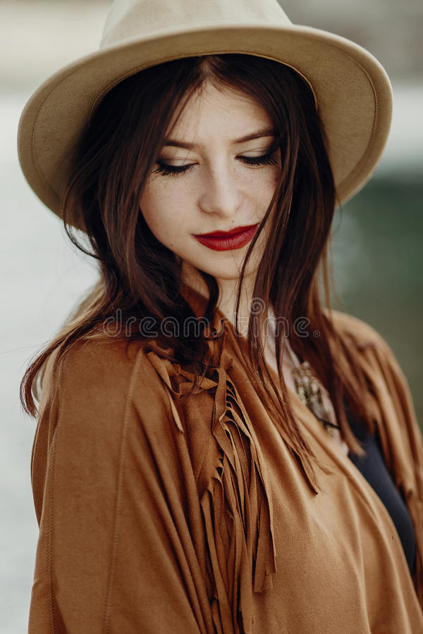 beautiful stylish boho woman with hat, fringe poncho. girl in gypsy hippie look young traveler posing near river rocks in royalty free stock image