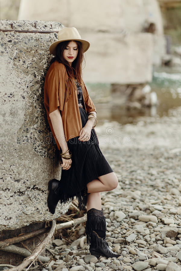 beautiful stylish boho woman with hat, leather bag, fringe poncho and boots. girl in gypsy hippie look young traveler posing near royalty free stock photo