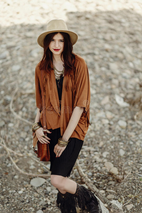 Beautiful stylish boho woman hipster with hat, leather bag, fringe poncho and boots. girl in gypsy hippie look young traveler. Posing near river rocks in stock photos