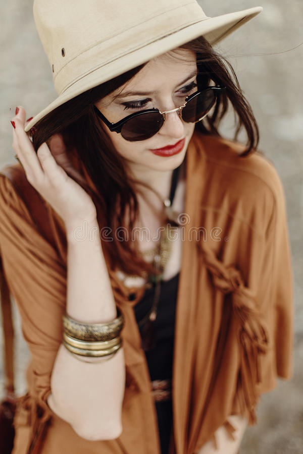 beautiful stylish boho woman in sunglasses and hat, fringe poncho and leather bag. hipster girl in gypsy look young traveler royalty free stock photo