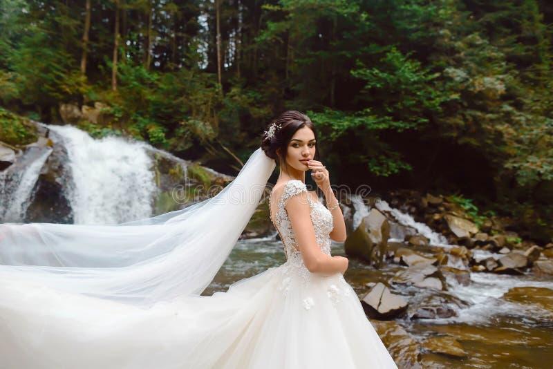 Beautiful stylish bride posing near the waterfall outside stock photo