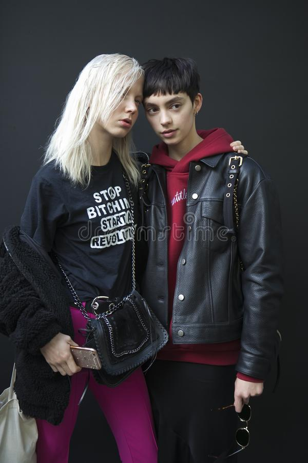 Beautiful and stylish Brunette and blonde, dressed in clothes in a sporty style, posing together during the London Fashion Week. o stock image