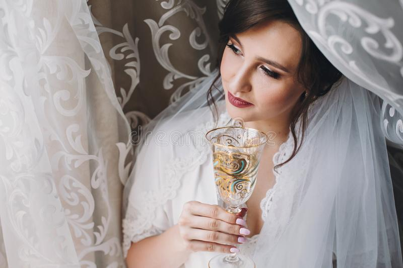 Beautiful stylish brunette bride posing in silk robe under veil with champagne glass in the morning. Happy woman model with stock image