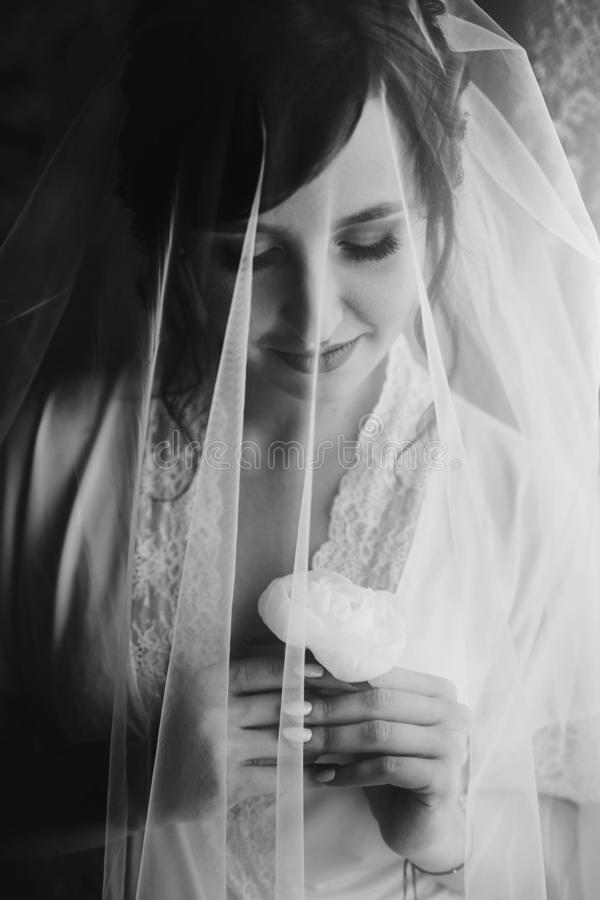 Beautiful stylish brunette bride posing in silk robe under veil in the morning. Sensual portrait of happy woman model with peony royalty free stock photography