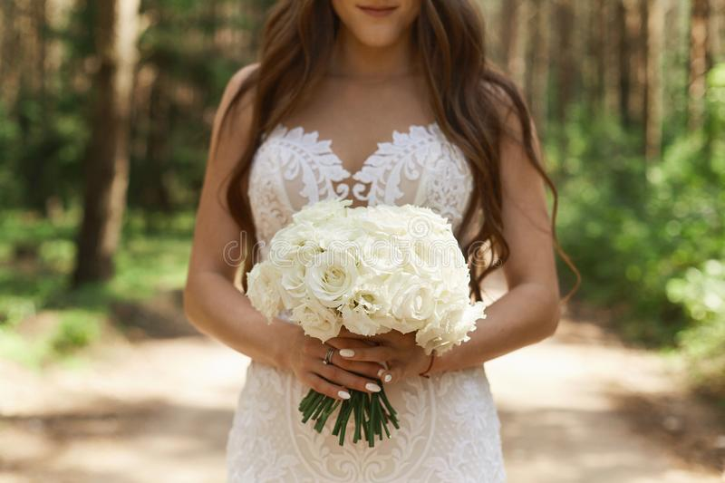 Beautiful and stylish brunette model girl in fashionable lace dress holding a bouquet of flowers in her hands and posing stock photos