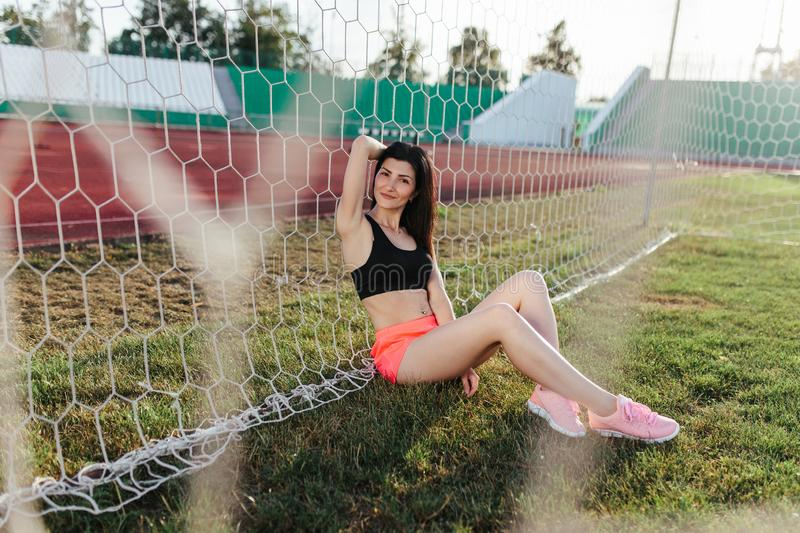 Beautiful stylish brunette woman in black top and pink shorts sitting on the lawn near a football goal at the stadium at sunset. stock image