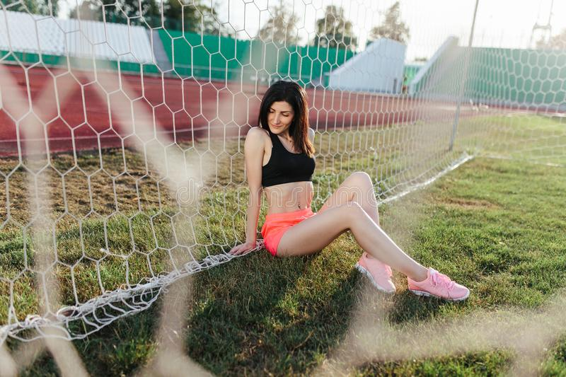Beautiful stylish brunette woman in black top and pink shorts sitting on the lawn near a football goal at the stadium at sunset. royalty free stock photo