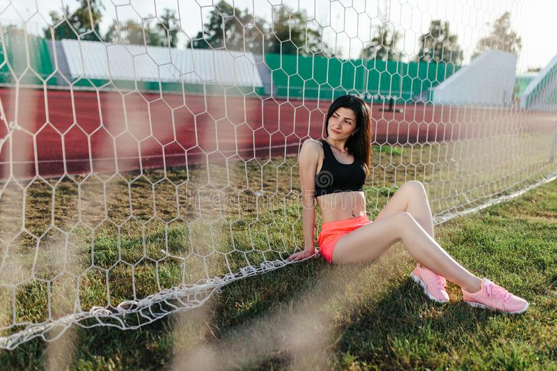 Beautiful stylish brunette woman in black top and pink shorts sitting on the lawn near a football goal at the stadium at sunset. royalty free stock images