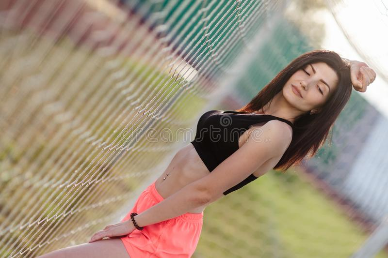 Beautiful stylish brunette woman with closed eyes in black top and pink shorts stands near a football goal at the stadium at royalty free stock photo