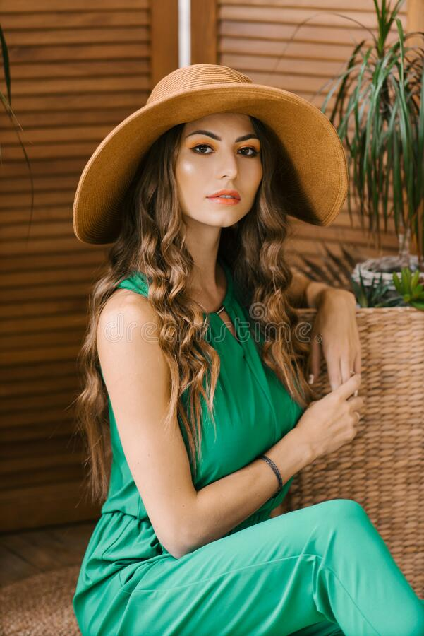 Beautiful stylish Caucasian girl with long hair and professional makeup in a wide brim hat in a green jumpsuit.  royalty free stock photo