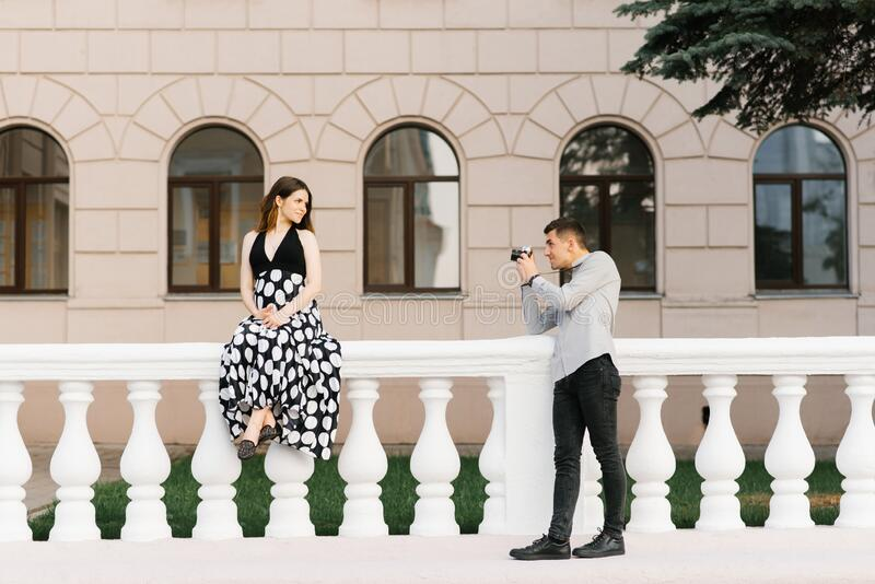 A beautiful stylish couple of future parents are walking around the city. The future father photographs the future mother.  royalty free stock images