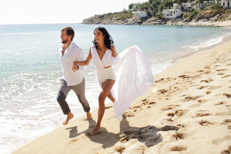 Happy romantic couple hold their hands and go on the beach in Greece, the honeymoon vacation, sunny day in the summer. stock photos
