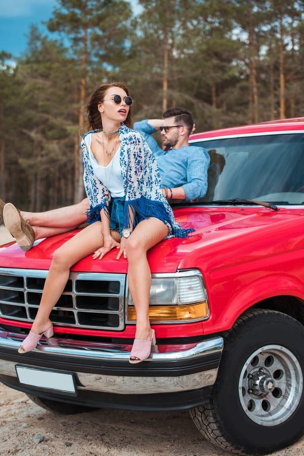 beautiful stylish couple sitting on red car stock photo