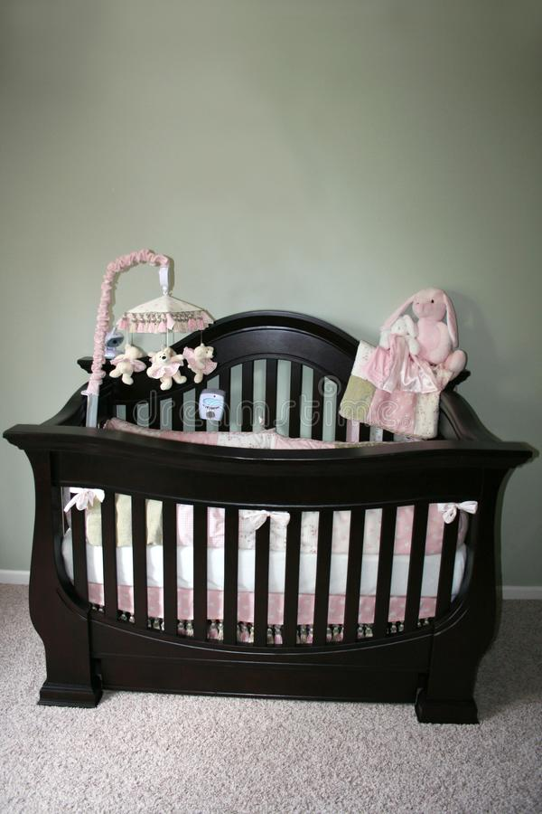 Pretty Little Crib. A beautiful stylish dark wooden crib with pink accents and a baby mobile stock photo