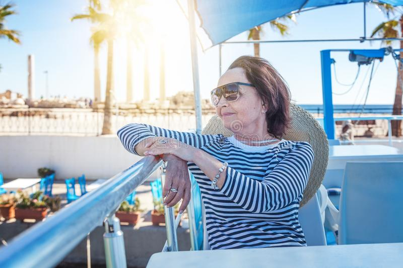 beautiful stylish elderly woman travels on a yacht, on a background of a resort and the sea. Active pensioners, vacations, travel royalty free stock photo