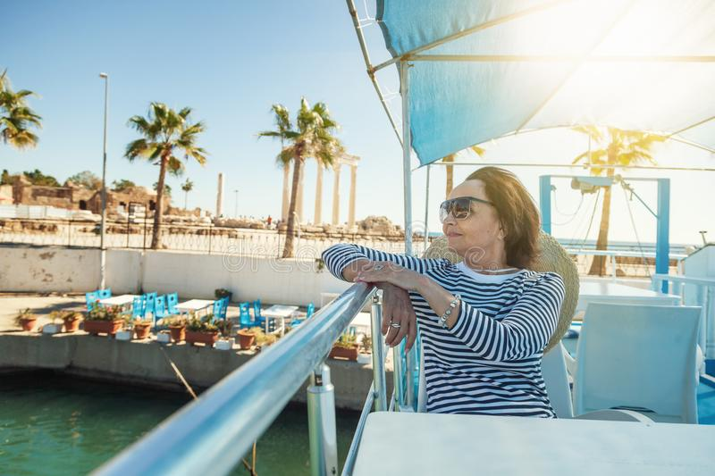 beautiful stylish elderly woman travels on a yacht, on a background of a resort and the sea. Active pensioners, vacations, travel stock photography