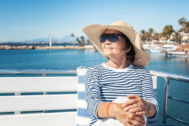 beautiful stylish elderly woman travels on a yacht, on a background of a resort and the sea. Active pensioners, vacations, travel stock images