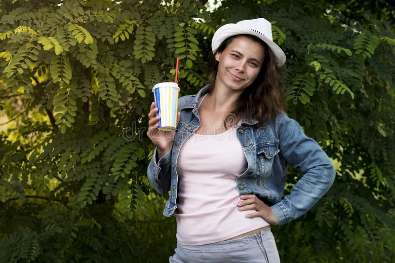 Beautiful stylish fashionable young girl in park with cocktail and straw in her hand. nice woman in hat and jeans jacket in nature stock image
